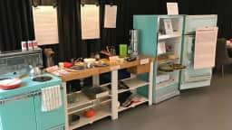 Dans une cuisine, une réfrigérateur, une cuisinière et différents objets exposés.