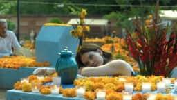 Une femme couchée dans un cimetière entourée de fleurs oranges et de chandelles