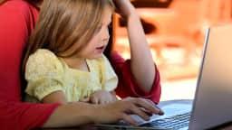 Petite fille assise devant un ordinateur