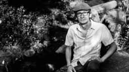 Photographie en noir et blanc du chanteur Roberto López, assis sur une roche.
