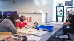 Trois personnes attablées, dont un enfant pointant l'écran d'une tablette numérique.