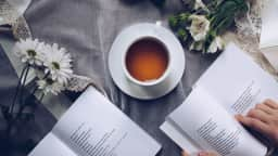 Livres sur une table avec tasse de thé.