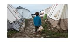 Photo d'un petit garçon devant des tentes
