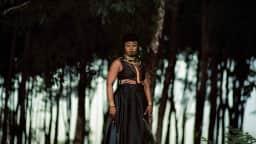 Une personne en habit traditionnel debout devant les arbres d'une forêt