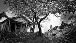 Photo en noir et blanc d'une femme balai à la main nettoyant le terrain devant sa maison