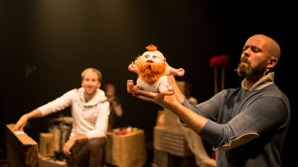 acteur manipulant une petite marionnette à barbe rousse