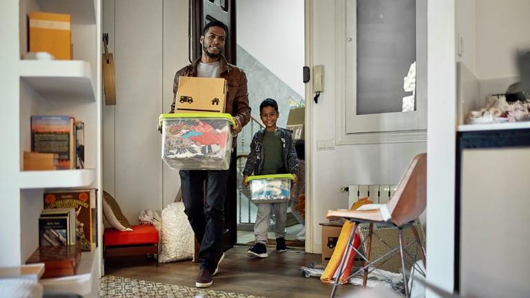 Un père et son fils transportent des boîtes de déménagement.