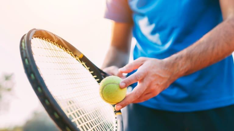 Un homme tient une raquette de tennis et une balle.