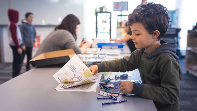 Un garçon feuillette des instructions et manipule du matériel informatique