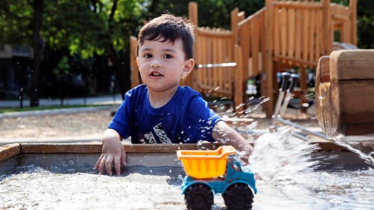 Petit garçon jouant dans un bac à sable avec camion