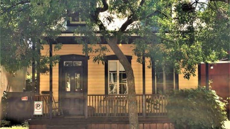 Maison jaune et brune patrimoniale entourée d'arbres
