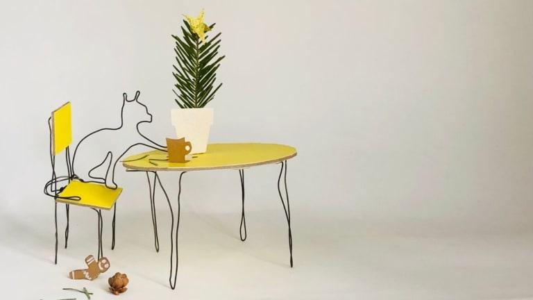 Petit fait en fil de fer buvant un café assis sur une chaise jaune