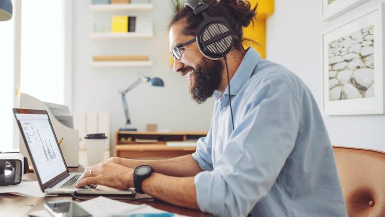 Jeune homme portant un casque d'écoute et travaillant à l'ordinateur