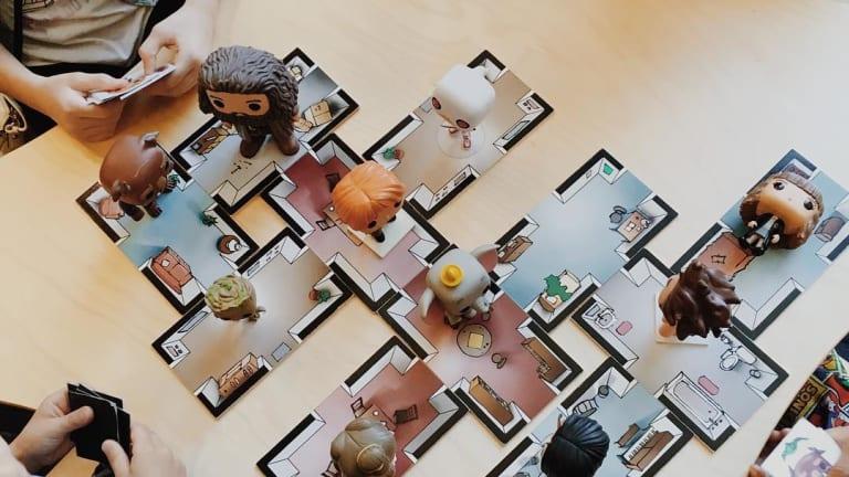 Un adulte et trois enfants sont attablés autour d'un jeu de société