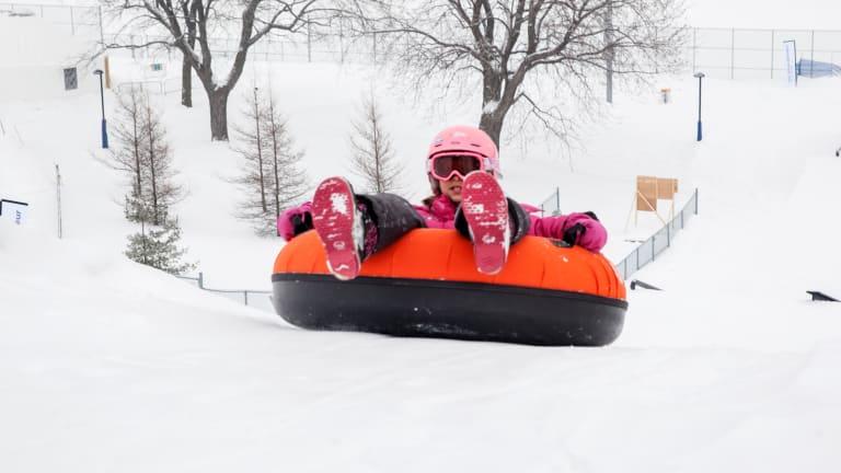 Un enfant en habit de neige dans un tube glissant d'une bute à neige