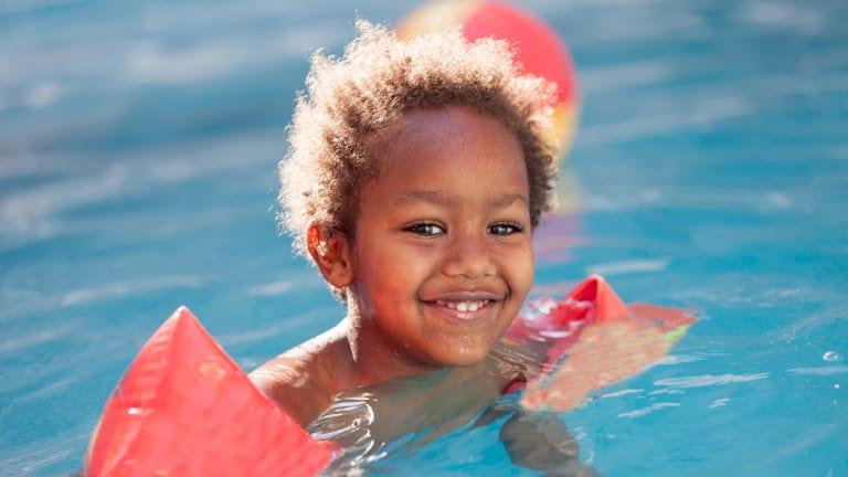 Un enfant issu de la diversité jouant dans une piscine extérieure