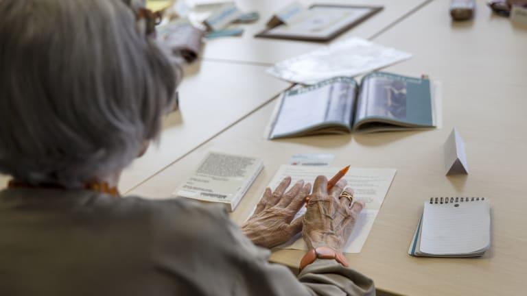 Femme âgée, de dos et attablée, les mains posées une sur feuille de papier