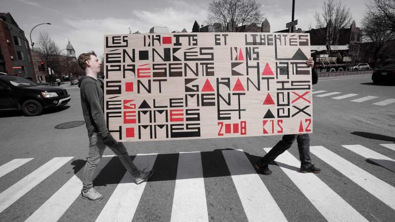 Deux personnes transportent un tableau sur lequel on voit un texte sur la charte