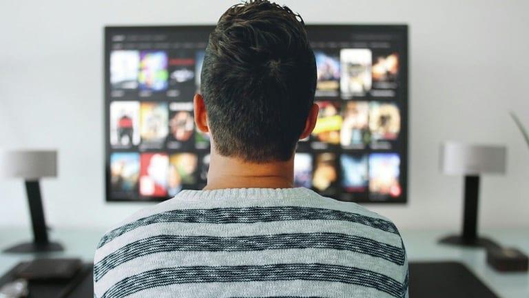 un homme assis devant un écran d'ordinateur sur lequel est diffusé de l'information