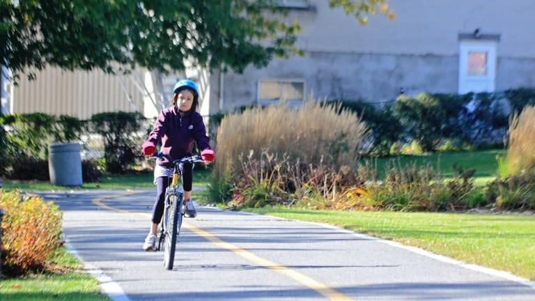 Fillette en vélo sur une piste cyclable.