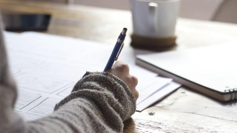 Photographie, gros plan sur une main tenant uns stylo, alors que la personne écrit