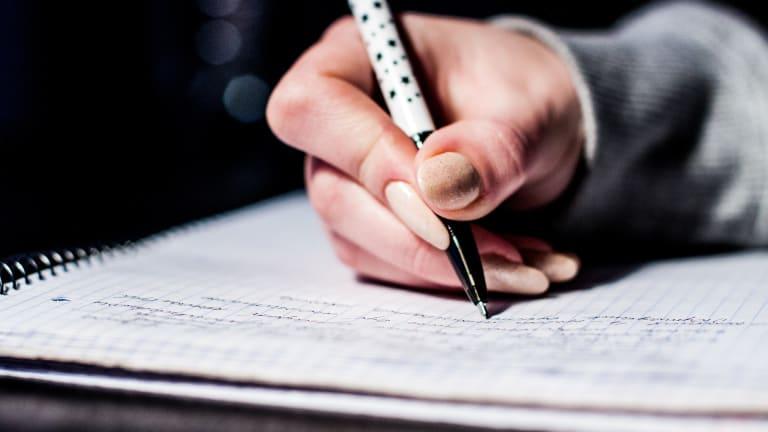 photo d'une main de femme tenant un stylo et écrivant dans un cahier