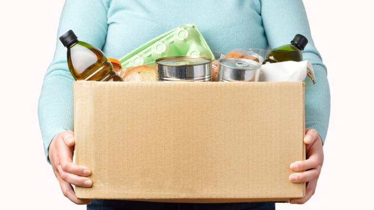 Personne qui tient dans ses bras une boîte remplie de nourriture