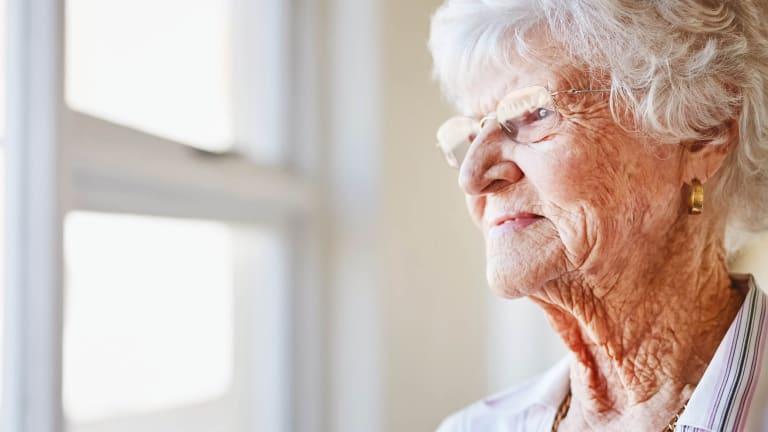 Une dame âgée regardant pas la fenêtre