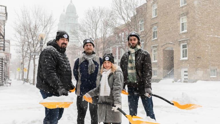 Membres et responsables de la Brigade neige, avec pelles en main, arborant fièrement une tuque MHM.