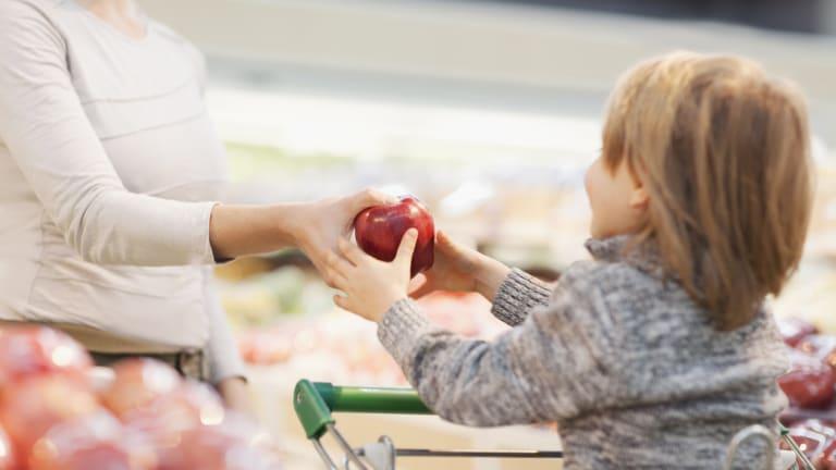 Une mère tend une pomme à son fils à l'épicerie.