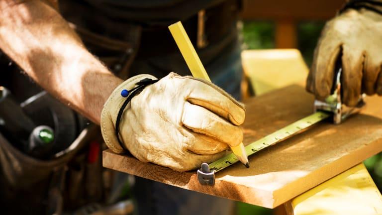 Un homme travaille et prend des mesures sur une planche de bois à l'extérieur de sa maison.