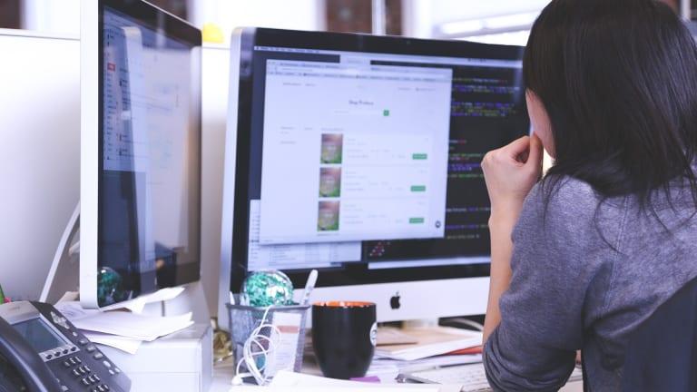 Une femme qui est assise devant un ordinateur