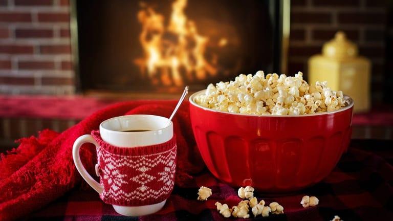 Tasse de chocolat chaud avec bol de maïs soufflé devant un feu de foyer