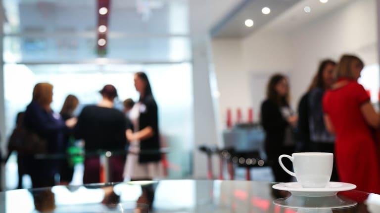 Photo d'une tasse de café, avec personnes discutant en arrière-plan