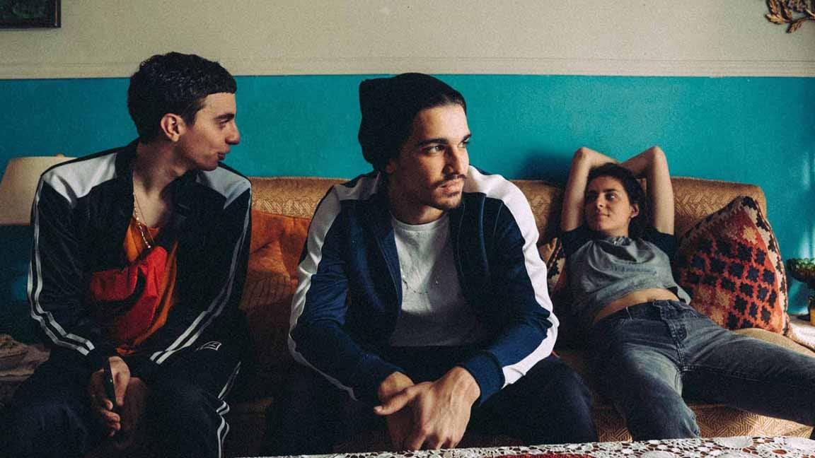 Photo d'un extrait du film Antigone, montrant trois jeunes sur un divan.