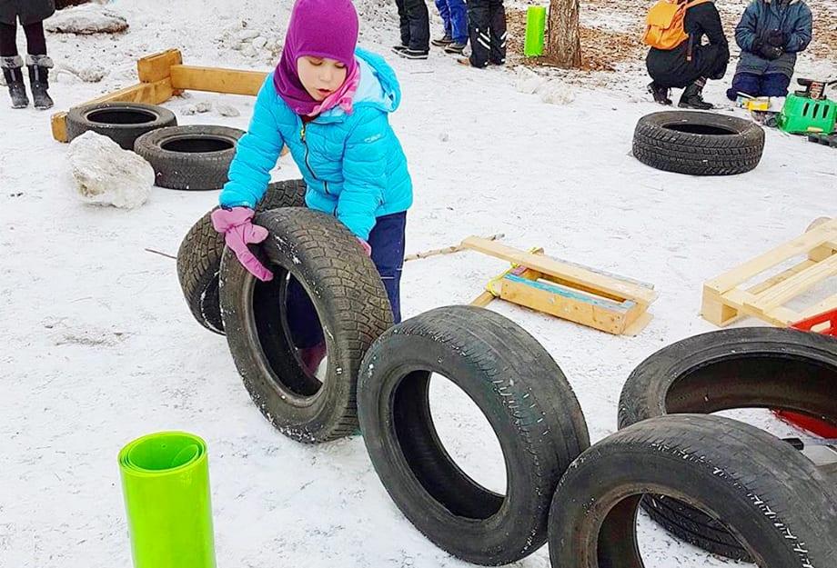 enfant jouant avec des pneus de voiture sur un terrain enneigé