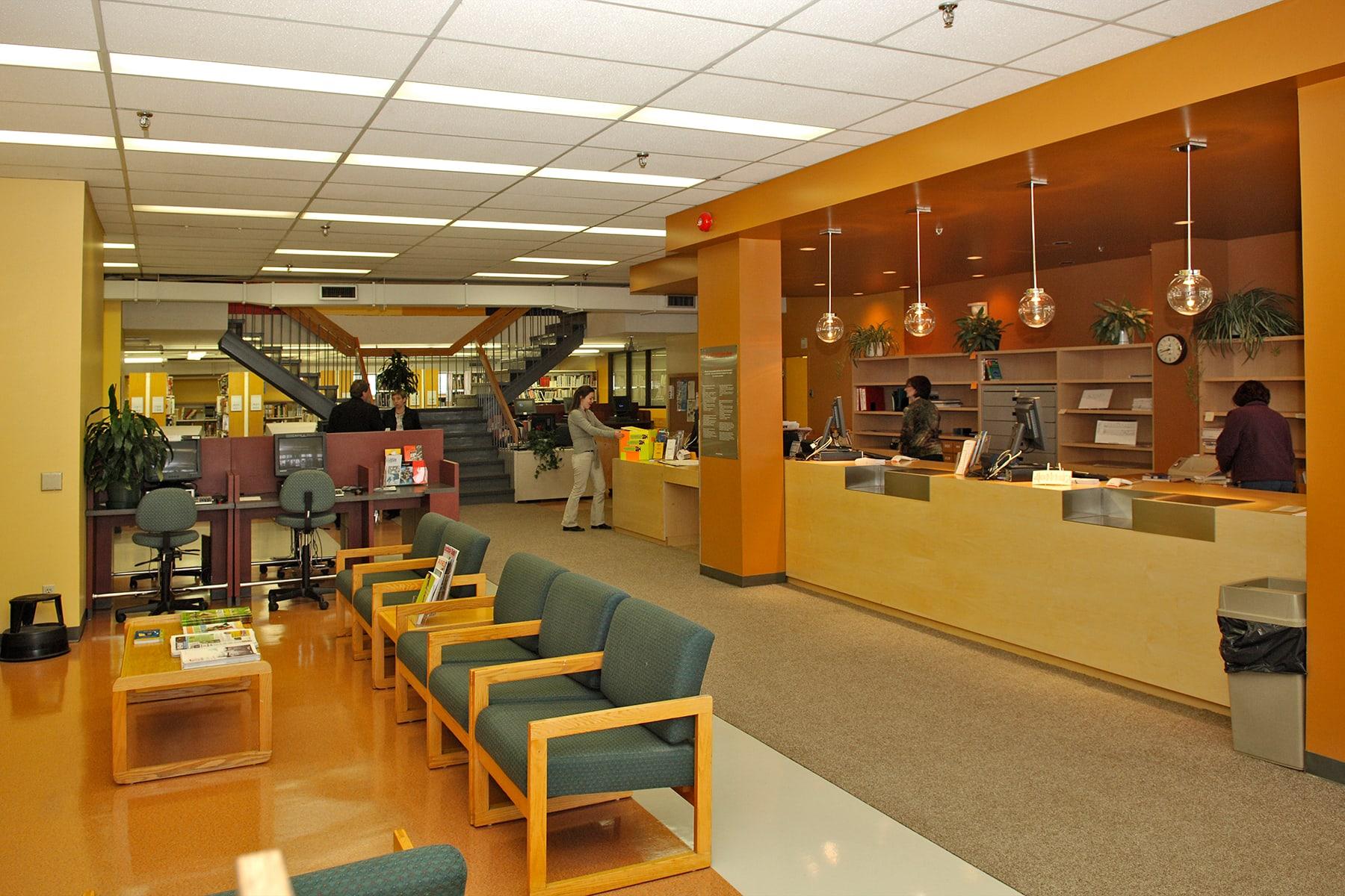 Intérieur de la bibliothèque Langelier - Comptoir d'accueil, aire de lecture et bibliothèques en arrière-plan