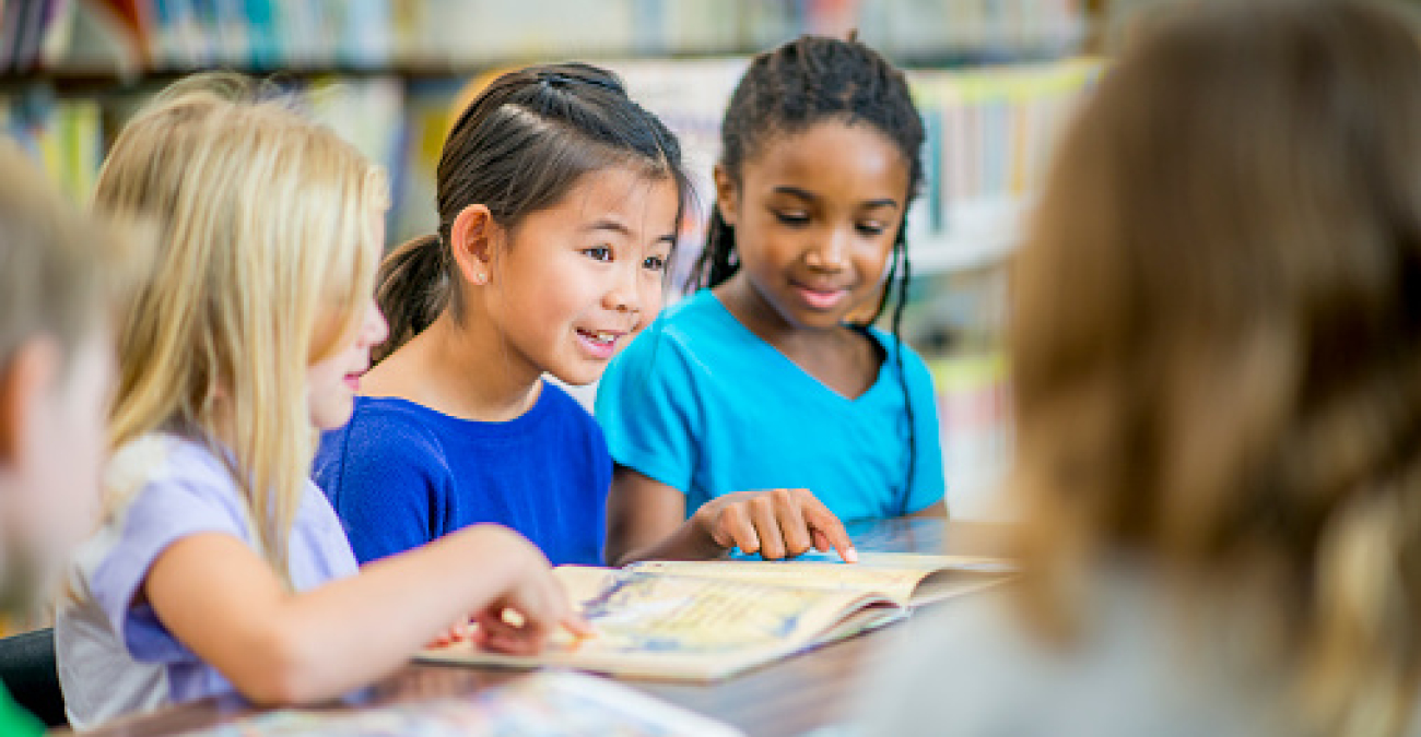 Three little girls read a book in a library. Two of the girls point to the contents of the book.