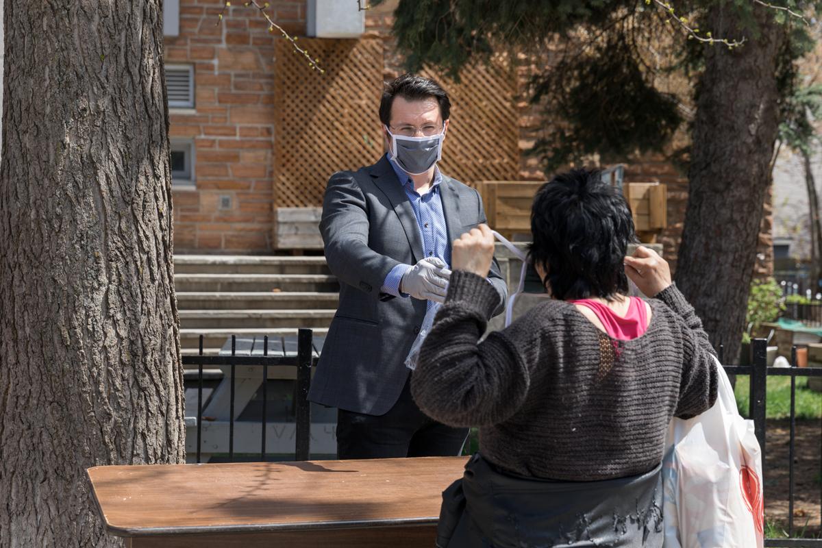 Pierre Lessard-Blais montrant à une dame comment bien mettre le masque.