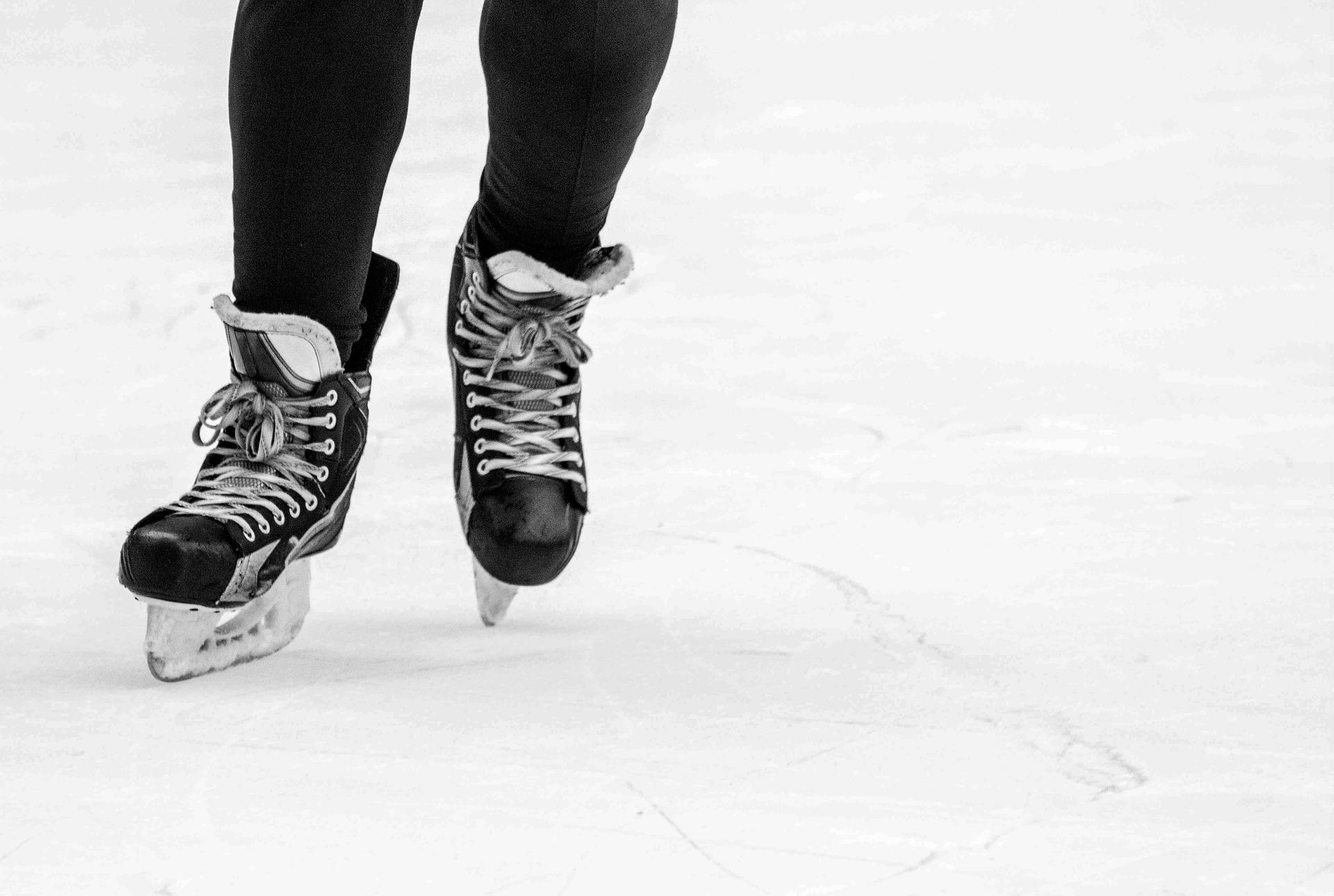 photo de deux pieds chaussés de patins noirs sur la glace extérieure