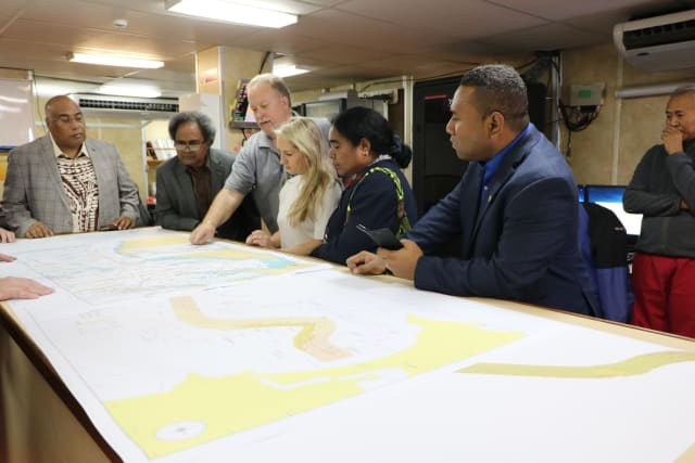 Collin Beck (High Commissioner Solomon Islands), Leo Oaeke (Consul PNG), Steven Onley (ASN), Sara Goldsworthy (DFAT), Victoria Oaeke (wife of Consul PNG) & Walter Diamana (Deputy High Commissioner Solomon Islands), looking at a map for the proposed path of CS².