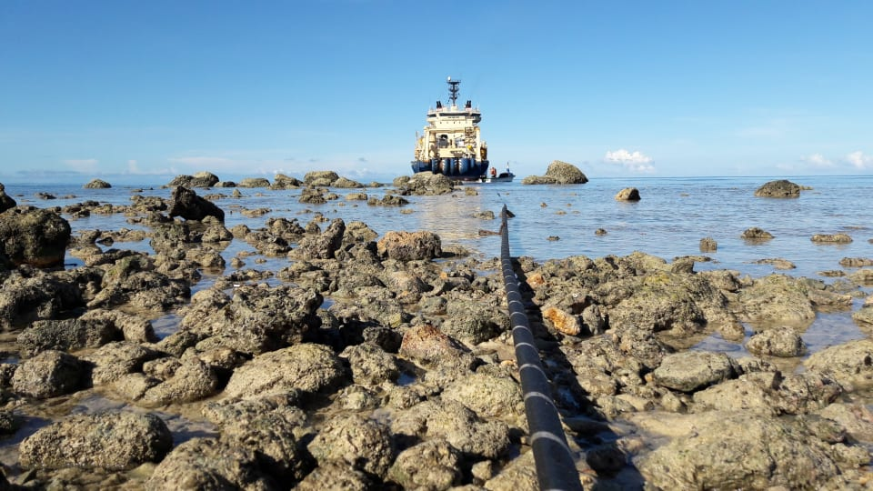 The Solomon Islands Domestic Network cable is floated ashore at Noro from the specialist cable-laying vessel the Ile de Brehat.  The cable can be seen in the foreground (Credit: Simon Cluer, ASN)