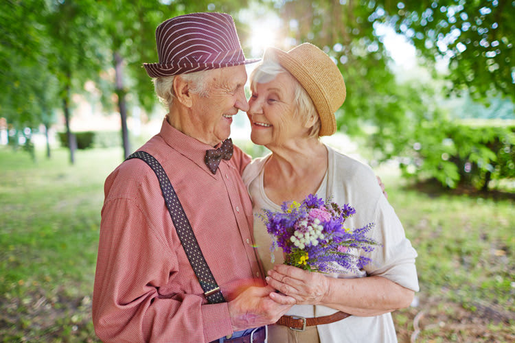 Old couple in fruit orchard