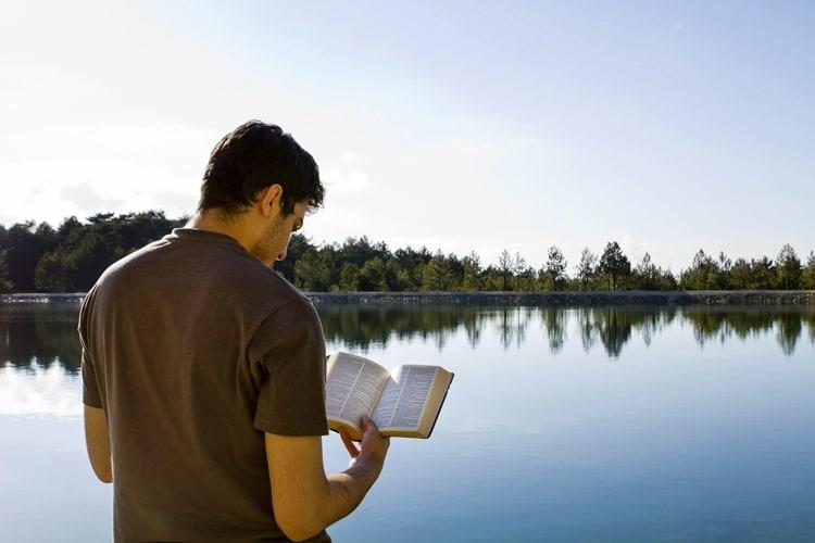 Man reading bible by a lake
