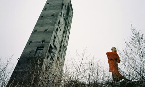 Cate Le Bon stood outside in a red coat next next to a grey, derelict tower.