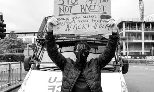 A young black man wearing a mask sits on a police van's bonnet holding up a protest banner