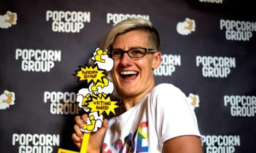 Jennifer Lunn smiling holding up an award for writing