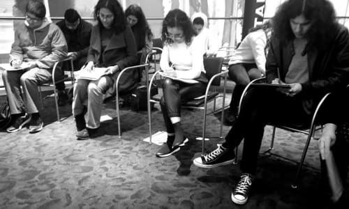 A group of young people sat down writing