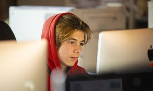 A teenage boy wearing a red hoodie sat at a computer screen