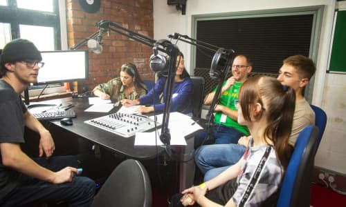 A group of young people sat in a radio station talking